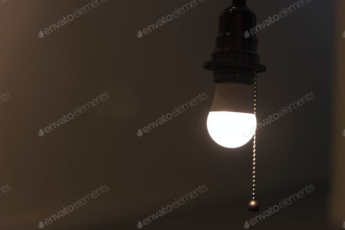 A bright light bulb hanging in a room