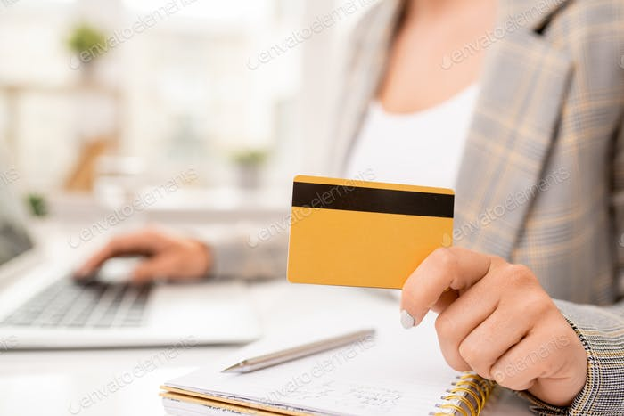 Yellow credit card with black magnet line held by contemporary businesswoman