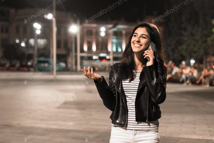 Young brunette talking on phone in the city centre at night