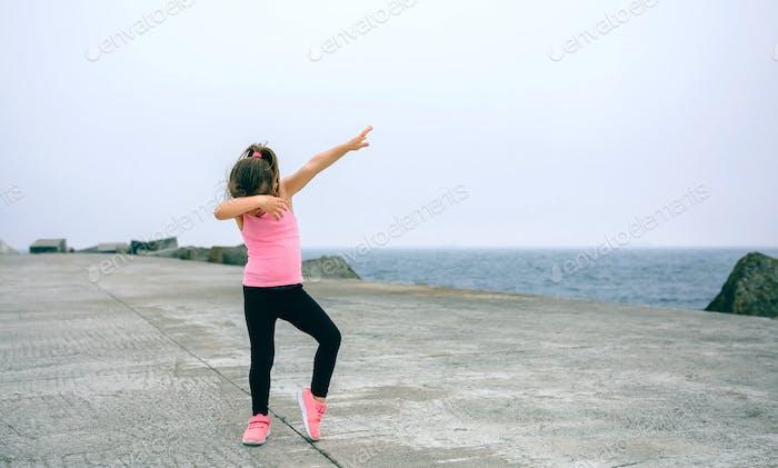 Little girl making dab dance outdoors