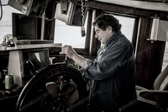 Ships captain at the wheel of a commercial fishing vessel.