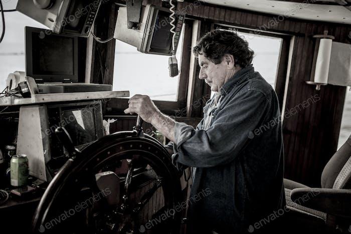 Schiffskapitän am Steuer eines kommerziell Fischereifahrzeugs.