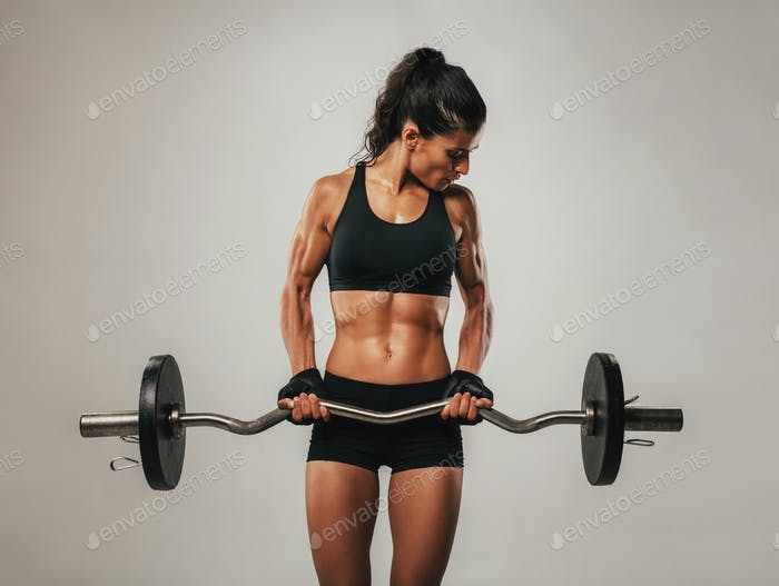 Muscular woman using barbell looking at her arms