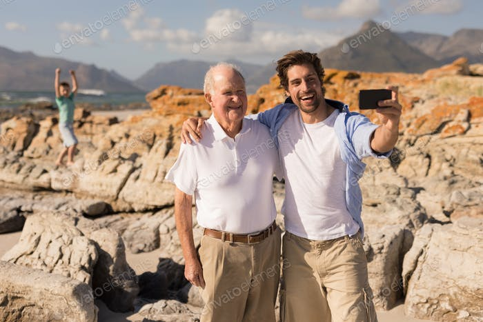 Front view of happy father and son with arms around taking selfie with mobile phone on beach