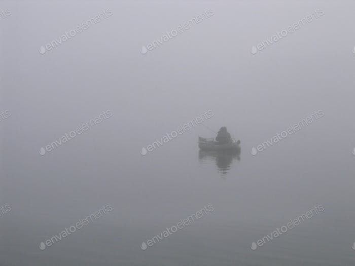 Lone fisherman on the river in a fog