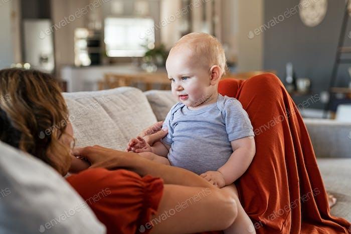 Lindo bebé sentado en el estómago de la madre