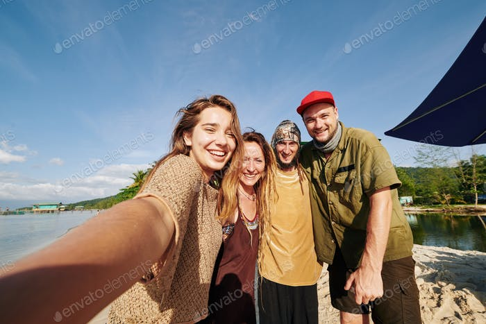 Young people posing for selfie on beach
