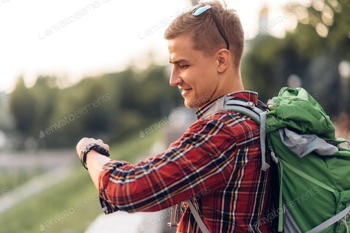 Male tourist with backpack looking at the clock