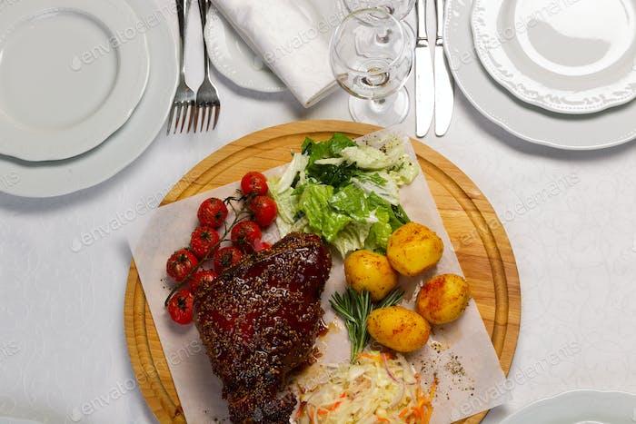 Fleisch mit Beilage von Gemüse auf einem Holzbrett, Draufsicht
