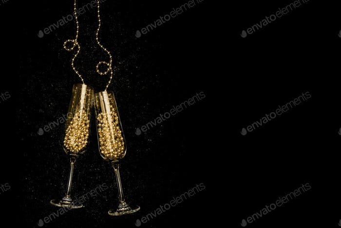 Glasses with champagne on black background. Christmas and New Year celebration