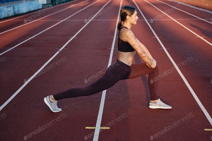 Attractive sporty girl in sportswear doing stretching exercises on city stadium
