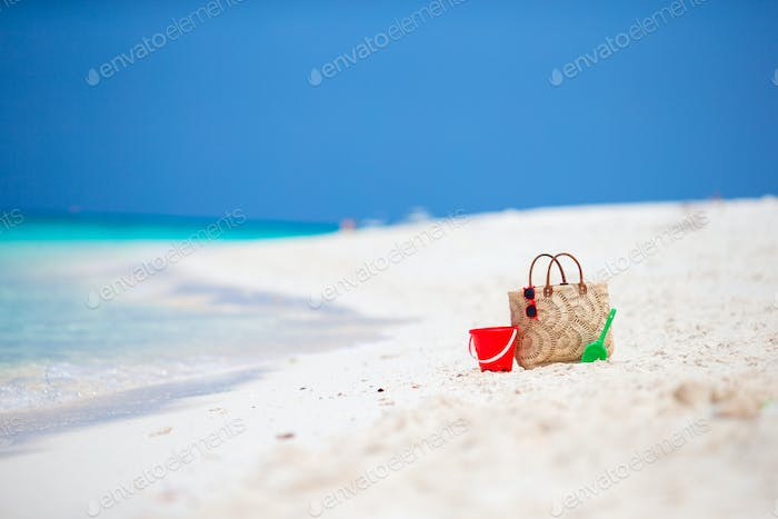 Beach accessories - straw bag, headphones, beach kids toys and sunglasses on the beach