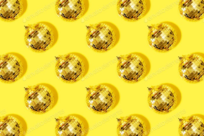 Creative Christmas pattern. Shiny gold disco balls over yellow background. Flat lay, top view. New