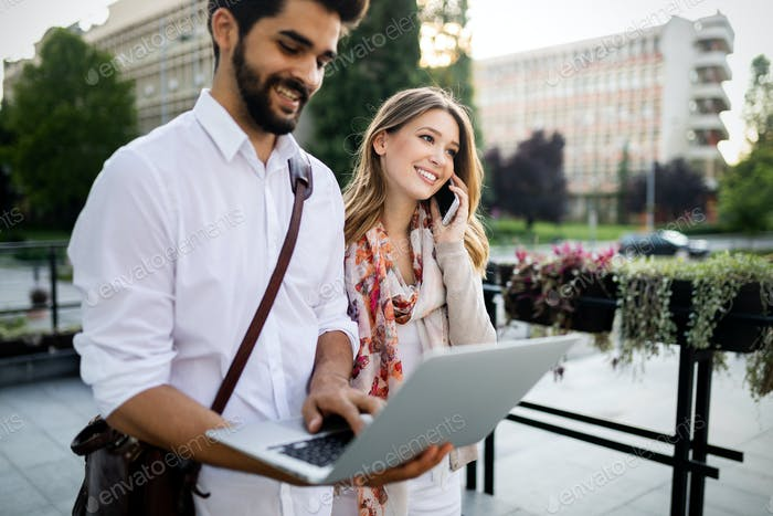Cheerful happy couple using digital tablet outdoors