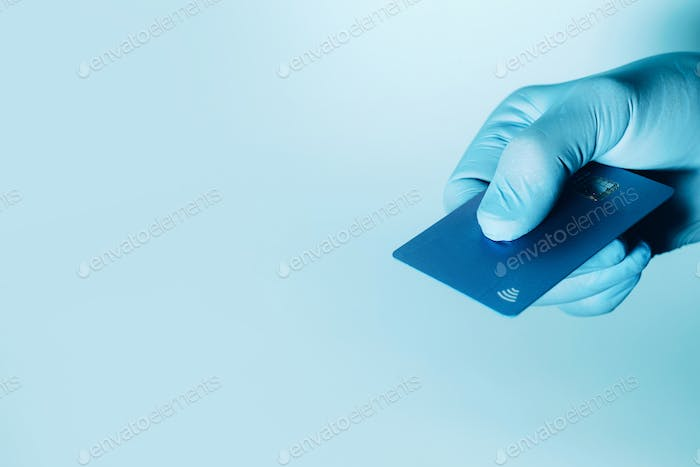 Hand in protective gloves holding credit card with contactless symbol, electronic chip. Online