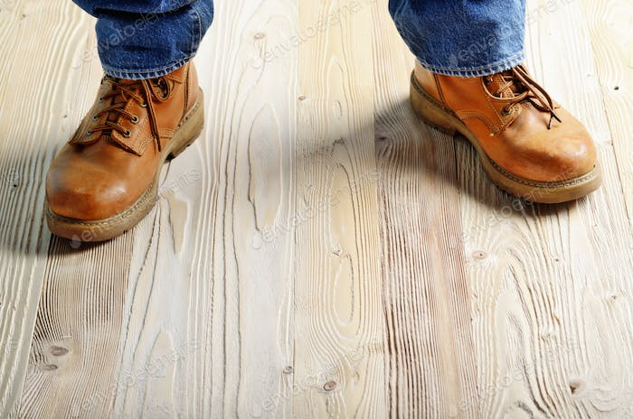 Carpenter feet in work boots standing on wooden floor. Place for