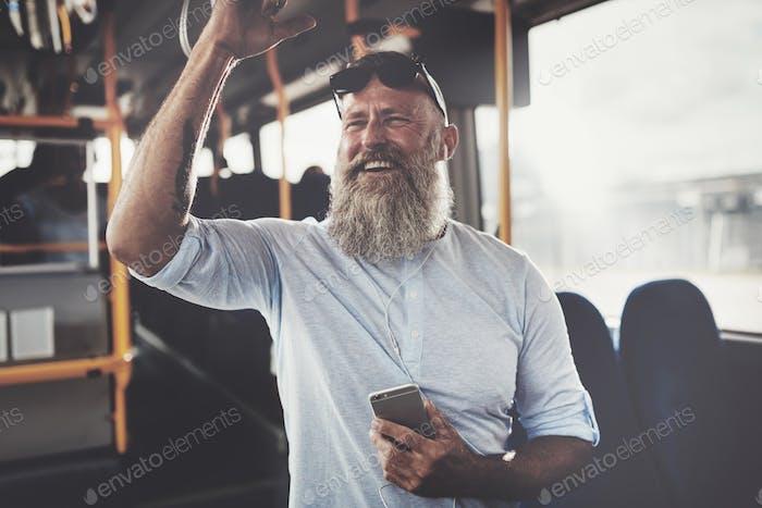Smiling mature man Reiten einen Bus Musik hören