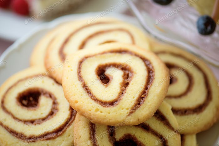 Close up of spiral cookies laid on white plate.