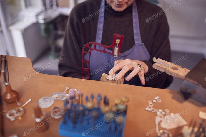Close Up Of Female Jeweller Working On Piece With Saw In Studio