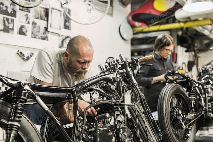 Zwei Männer reparieren Retro-Motorräder in der Werkstatt