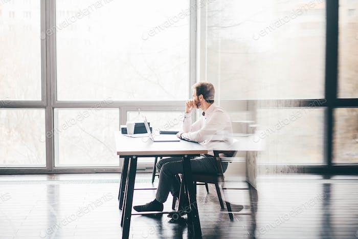 Junger Geschäftsmann sitzt am Tisch und schaut an das Fenster und denkt an modernes Büro.