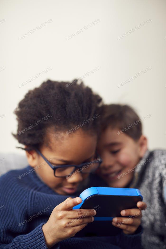 Dos chicos jugando juntos en dispositivos de mano en casa