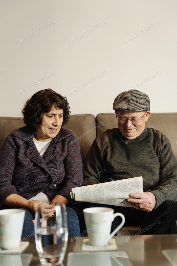 Elderly couple reading a newspaper.