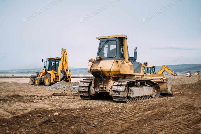 Industrial motor grader and backhoe excavator on highway construction site