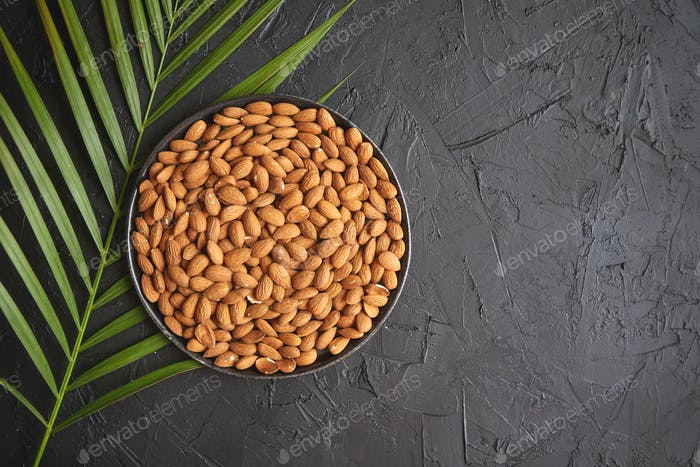 Composition of Whole almond nuts in black plate placed on black stone table