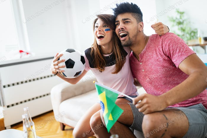 Excited couple watching tv together sitting on a sofa in the living room