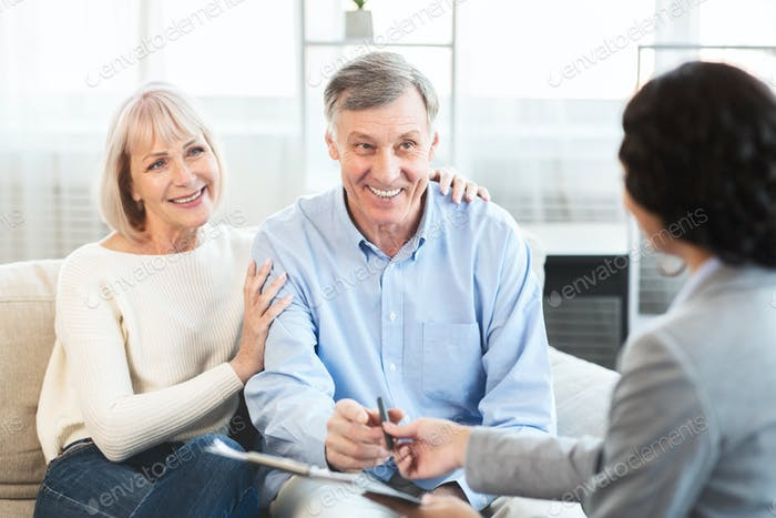 Happy mature couple talking to financial advisor at home