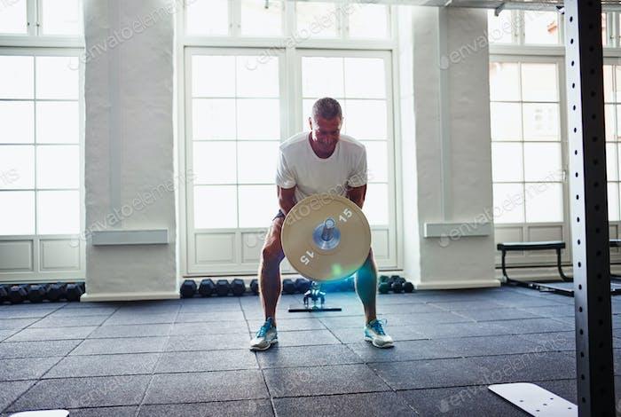Mature man in sportswear weightlifting alone in a gym