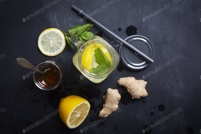Ginger Water in Glass jar With Lemon and Honey on a Black Background, Top View