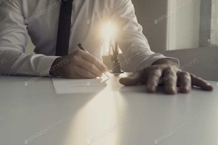 Businessman in white shirt signing document backlit by a shaft o