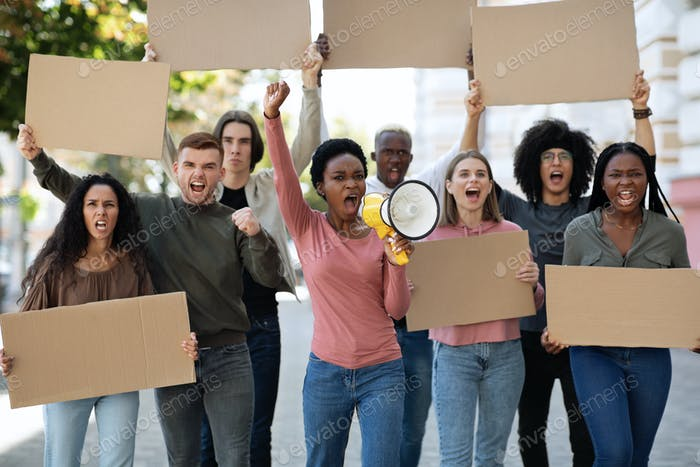Multiracial demonstrators striking on the street, holding megaphone and placards