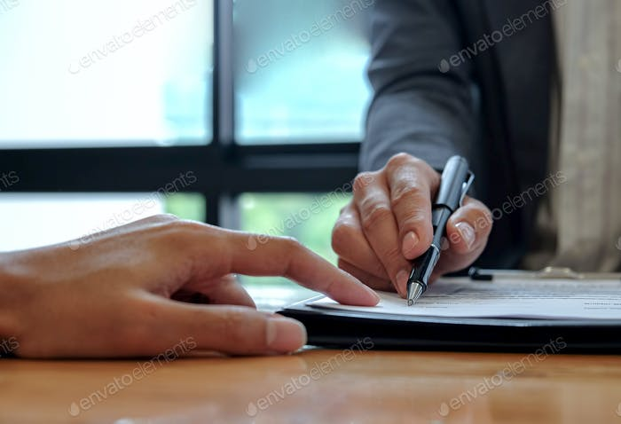 Seller hand point the customer to use the pen to sign the contract.