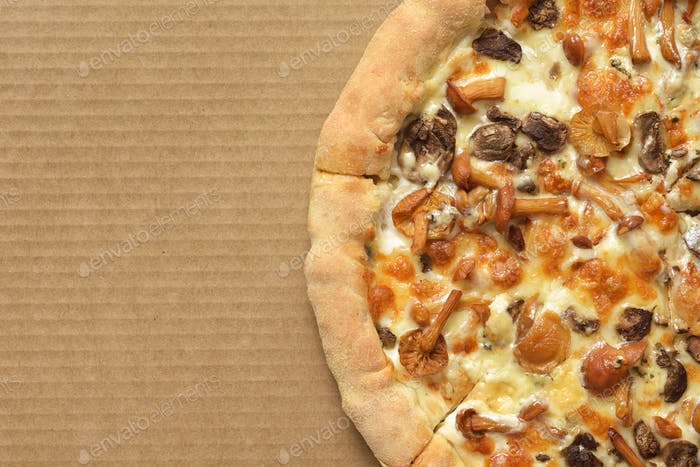 Pizza with mushrooms on corrugated fiberboard background.