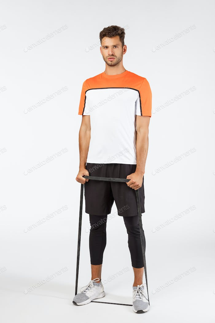 Vertical shot handsome bearded young male athlete in sportswear, football player workout during gym