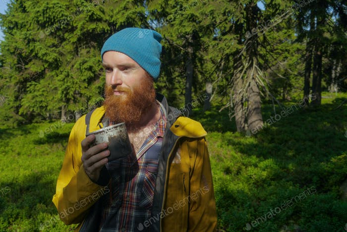 portrait of a caucasian male hiker standing in a forest holding a mug with coffee