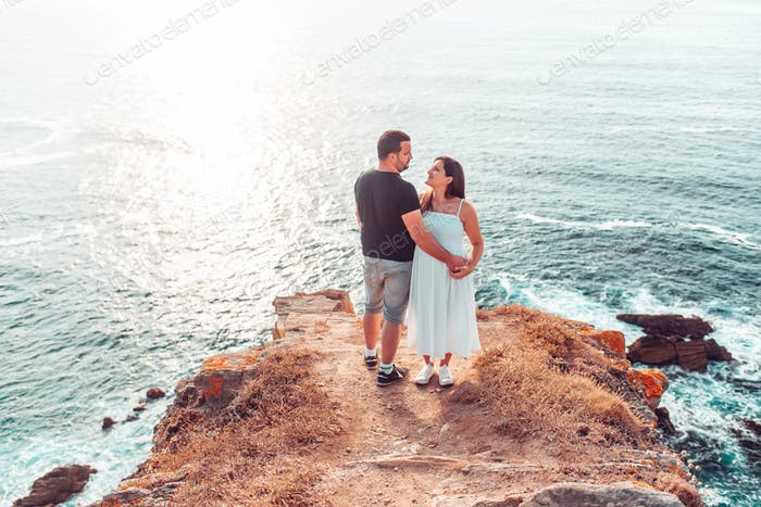 Couple looking at each other on top of a cliff