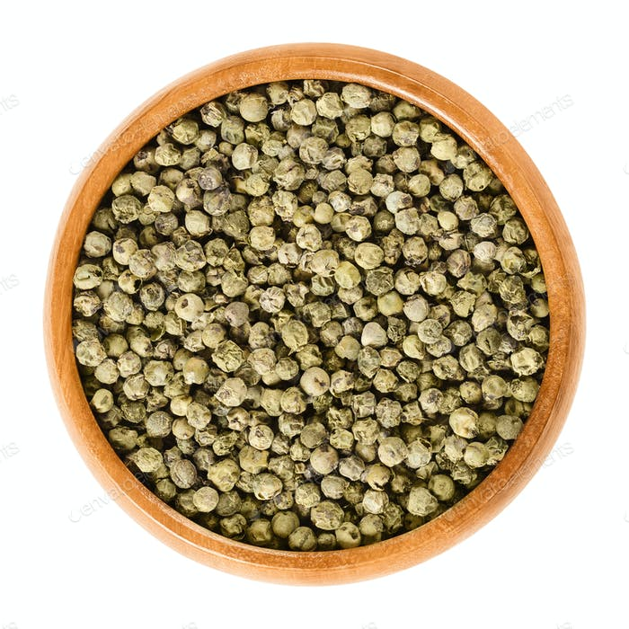 Green pepper in wooden bowl over white