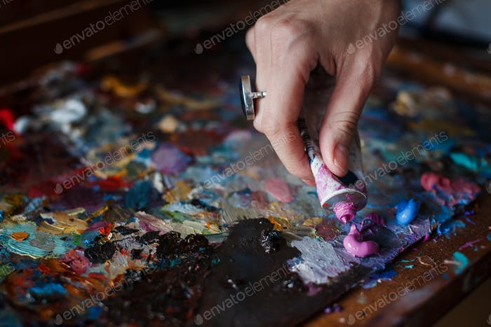 Artist's palette with multi-colored smeared colors and one brush.