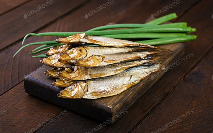Smoked sprat and green onion  on a cutting board on a wooden background. Smoked fish.