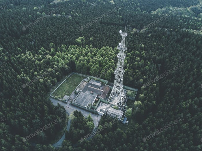 AERIAL: Drone Shot of old Abandoned Radio Tower Station in Rich Green Forest surrounded by Trees