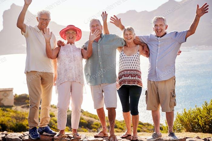 Vertical de mayores Amigos visitando punto de referencia turístico en Grupo de vacaciones con los brazos levantados