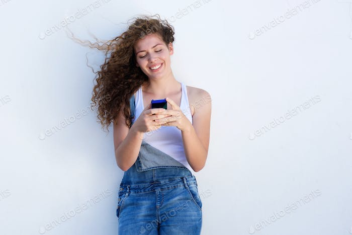 Happy teen holding cellphone and smiling with hair blowing
