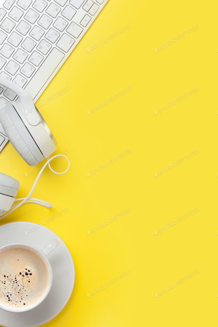 Office yellow workplace with coffee cup, headphones and pc