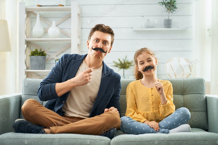 Father and daughter with moustache on stick.