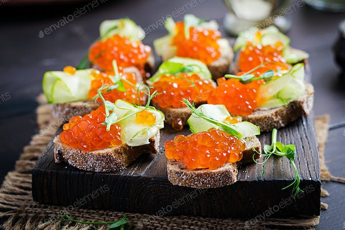 Canape with salmon red caviar. Sandwich for lunch. Delicious food.