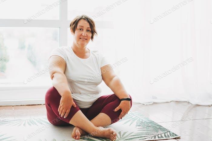 Adult charming brunette woman plus size body positive practice yoga